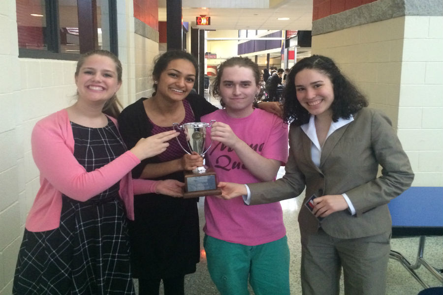 Forensics Speech officers hold up a symbol of their hard-earned victory.
