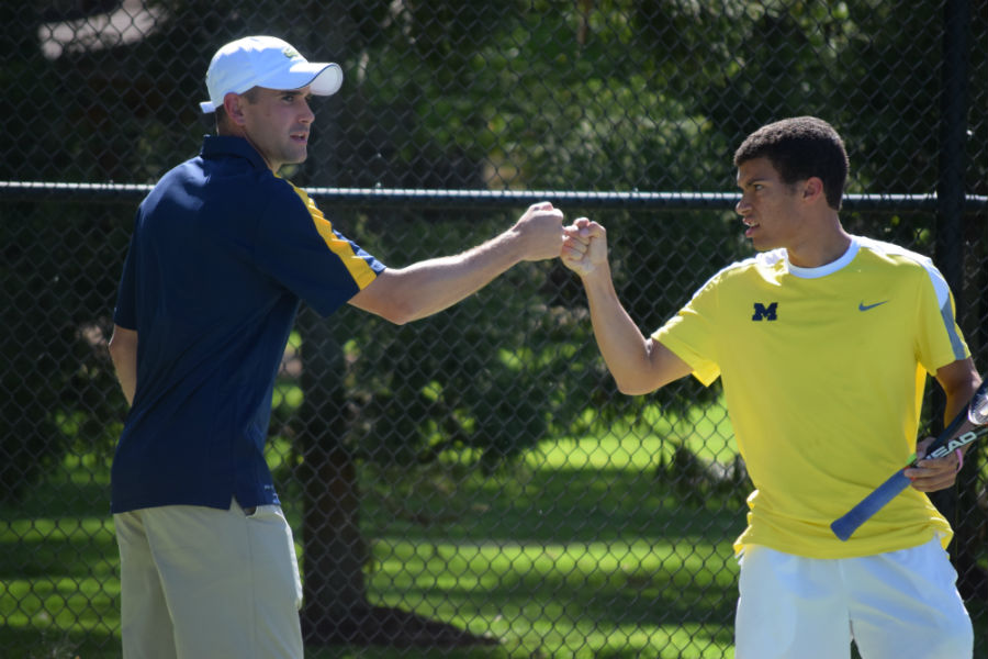 Senior Matthew Cousins gives Coach Brohl a quick fist pump on the court.
