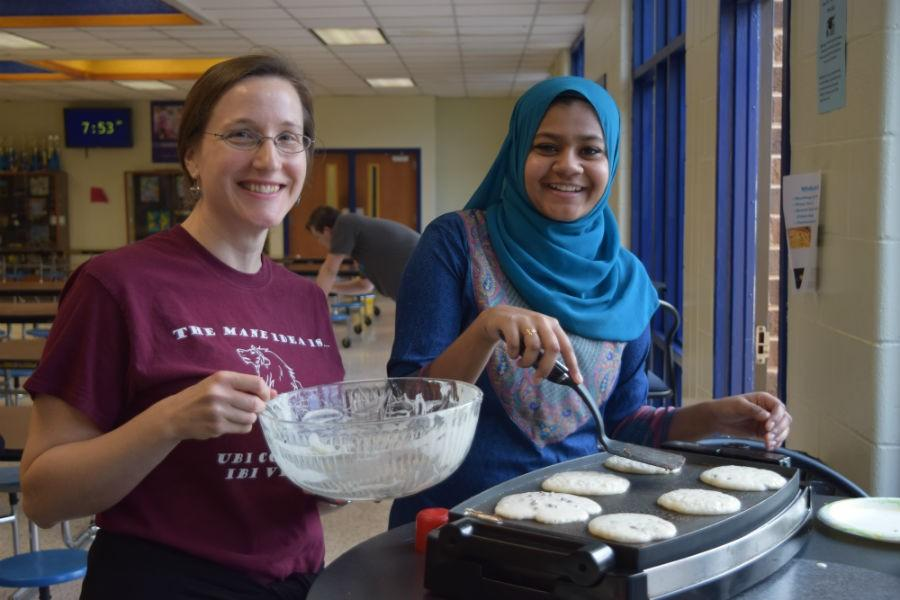 Mrs. Peterson and Mariha Junaid serve pancakes to Mrs. Austin's winning class.