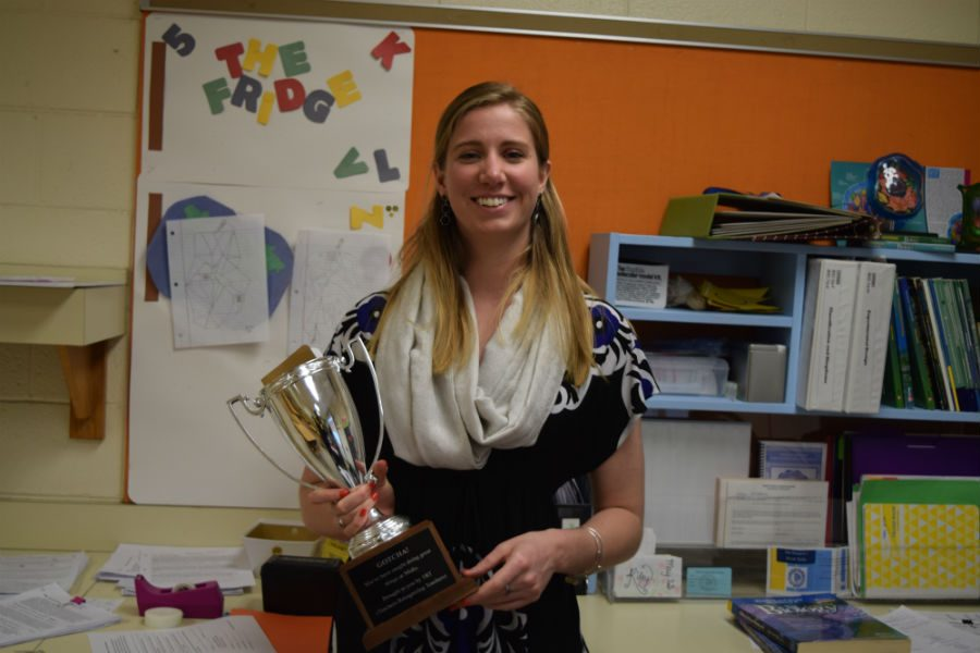 Ms.+Goins+shows+off+her+trophy+she+received+from+Mrs.+Williams+as+the+April+TRT+recipient.