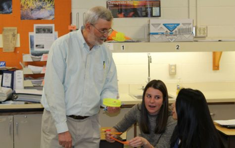 Mr. Pettis helps students Isobel Harrison and Mukti Patel with their assignment.