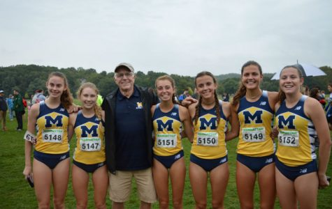 Cross Country ladies show their excitement with Coach Morgan following the race.