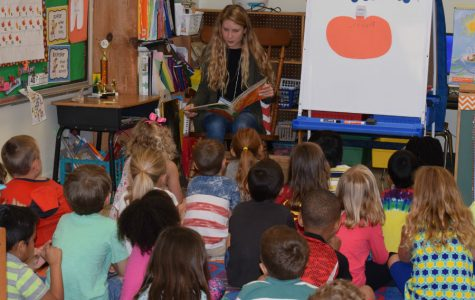 Junior Camryn Adams reads a pumpkin story to get her students in the Halloween spirit.