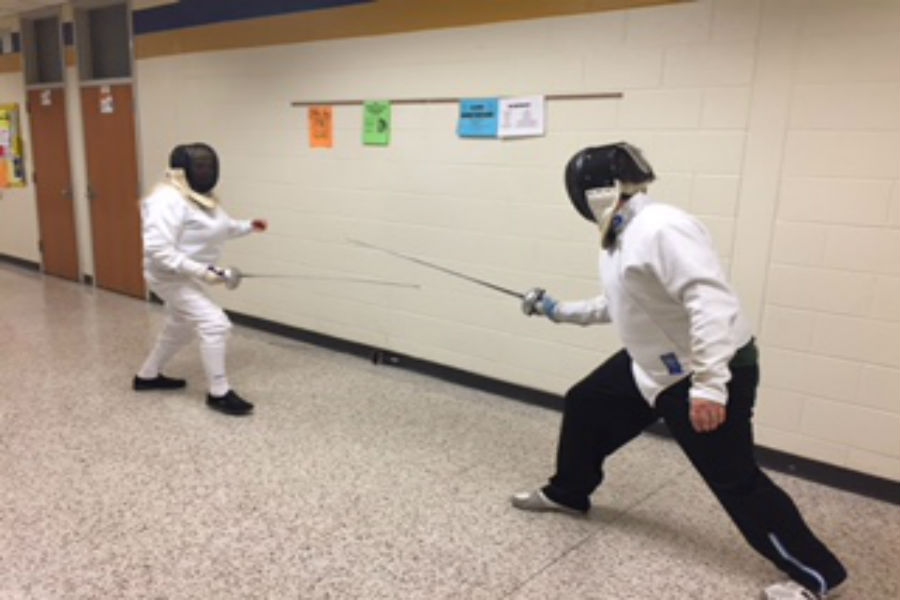 Two fencers demonstrate a live duel.