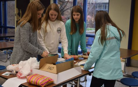 Abigail Graves, Claire Horansky, Ashley Manheim, and Caroline Leach help each other wrap the Spirit Club presents.