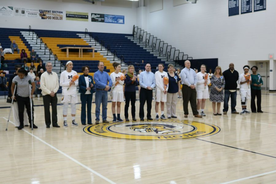 The+senior+members+of+the+girls+basketball+team+with+their+parents+receive+recognition+on+Senior+Night.