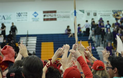 The senior class raises the spirit stick in the air.
