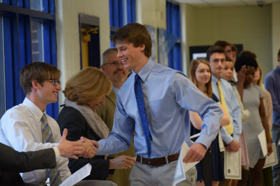 Eric Overby shakes Lucas Via's hand after receiving his NBHS certificate.