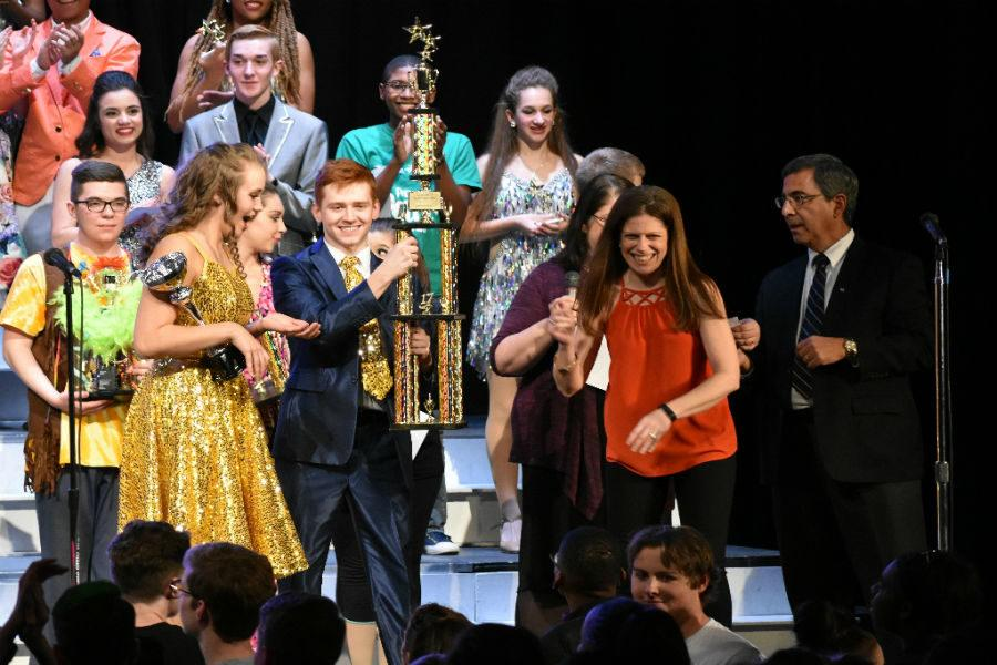Sean Dudley proudly accepts the first runner-up trophy at the awards ceremony at the close of the show choir competition.