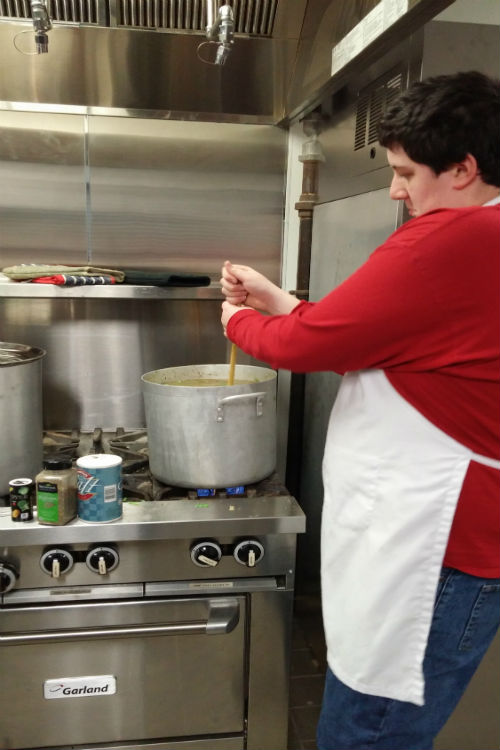 Ian Helm stirs the German Green Bean Stew to feed the guest during CARITAS.