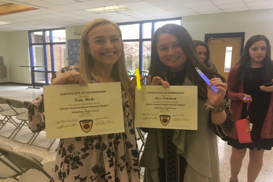 Kate Hicks and Elise Pritchard show off their SNHS certificates and glow sticks.