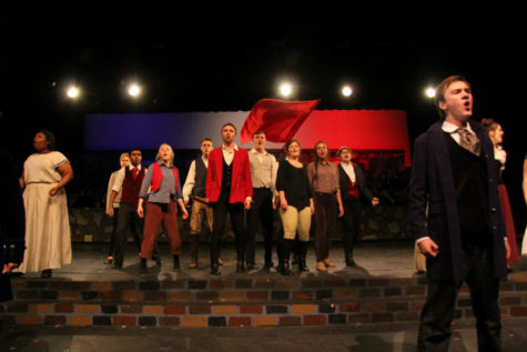 "Carter Seaborn, as Enjolras, leads the cast during ""One Day More"" in Les Mis."