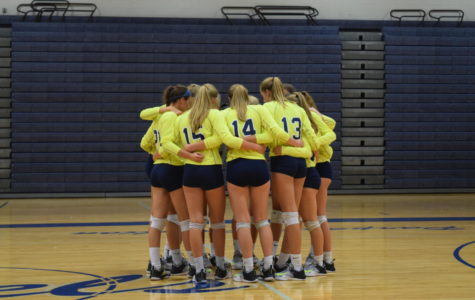 The Trojan girls volleyball team huddles together.