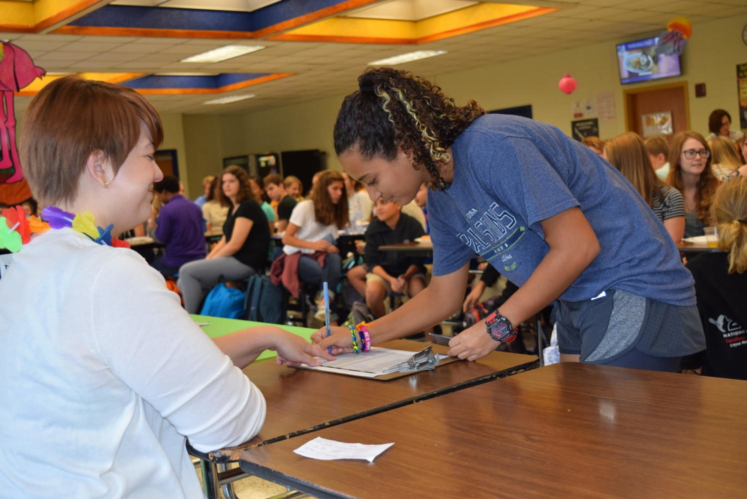 Assistant Librarian Emilia Mazzanti helps a student during the Summer Reading Celebration.