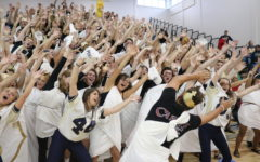 Seniors do the wave during the homecoming pep rally.