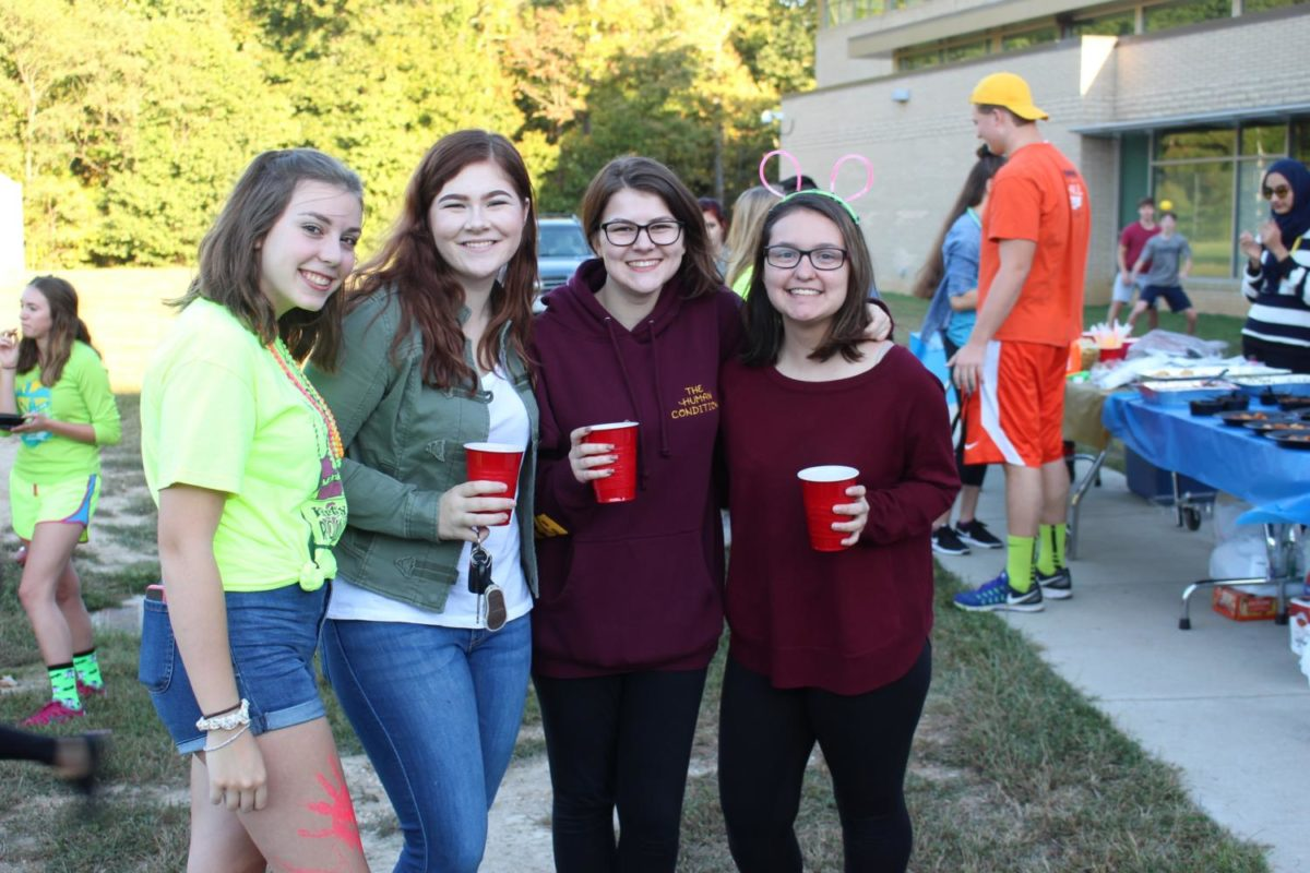 Hannah Walker, Meredith Puster, Madison Jardice, Erica Fuentes hang out at the tailgate.