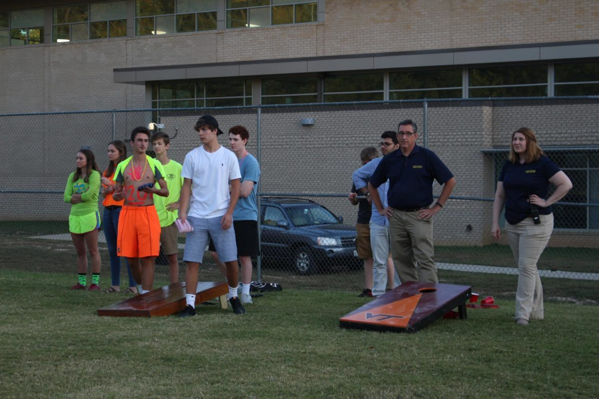 Seniors and faculty members gather to play a few rounds of corn hole.