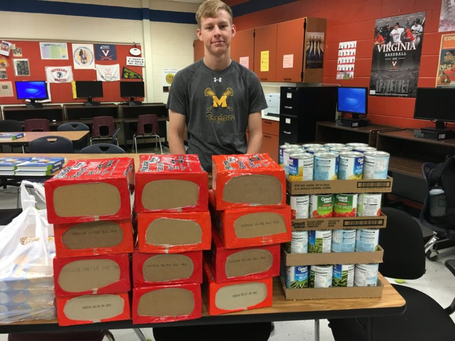 Jack Stid shows off the FBLA food collection for the Midlo vs. Monacan Food Fight.