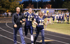 Senior quarterback Kyle Daniluk is escorted by his parents on Senior Night.