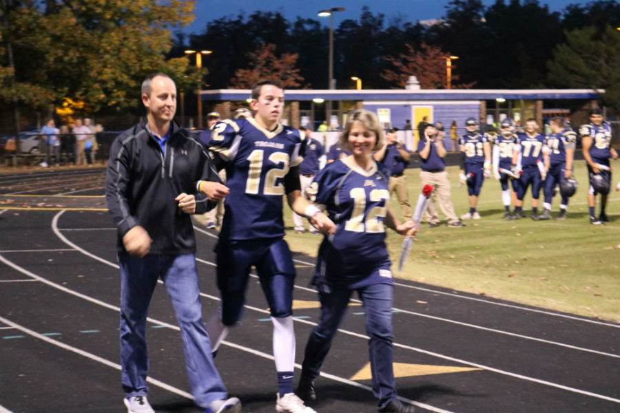Senior+quarterback+Kyle+Daniluk+is+escorted+by+his+parents+on+Senior+Night.