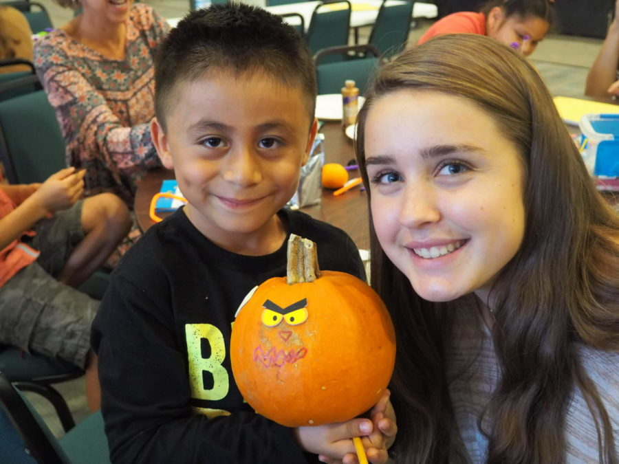 Hillary+Hettinger+and+her+Homework+Helpers+student+show+off+their+decorated+pumpkin.