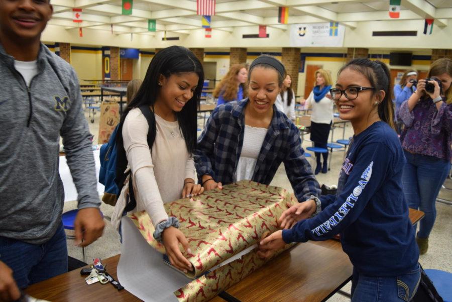Enjhalika Esmena, Maya Arrington , Milleena McNeil measure their wrapping paper during the Spirit Club Wrapping Party.