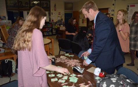 Mr. Abel contributes to the Trojans for Tomorrow's Kindness Kanes activity.