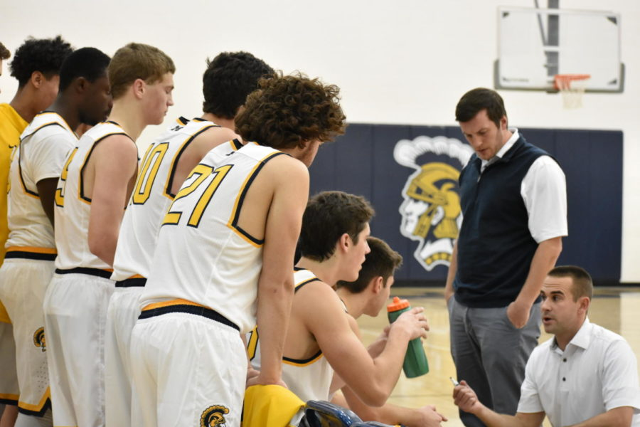 Members of the Midlo Varsity team listen to Coach Brohl during a timeout.