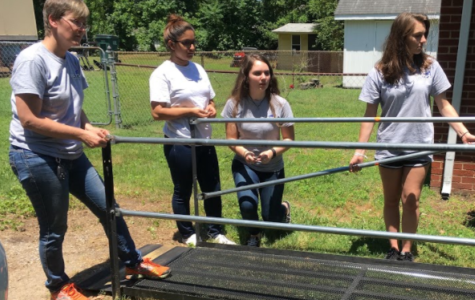 Students Carrie Rowley, Rachel Edwards, and now-high school graduate Mishaal Gilani assemble a ramp for RAMPS, a nonprofit organization that creates ramps for people with disabilities.