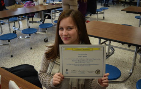 Caitlin Woods shows off her certificate marking her National English Honor Society induction.