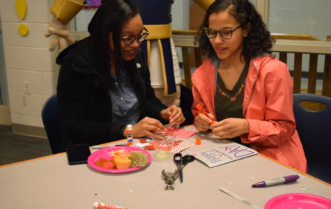 Ni'Asia Griffin and Hayden Hicks share materials and ideas while designing their cards.