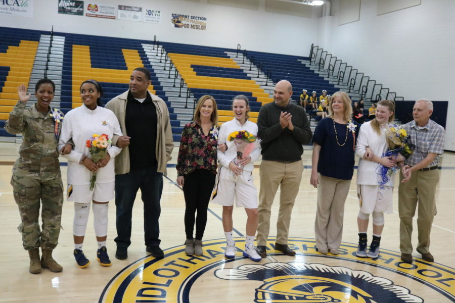 The celebrated seniors and their parents stand before the excited crowd.