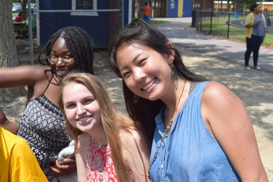 Joy Li, Merrill Livingston, and Jade Adelaja hand out popsicles to students.