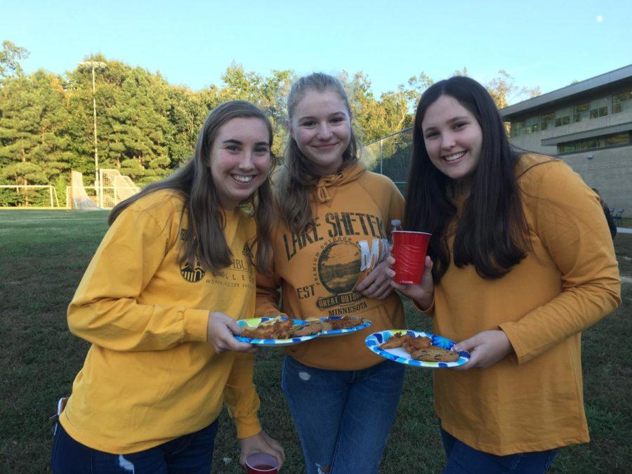 Elizabeth Czenczek, Greta Cusack, and Grace Wells savor the food provided by the Senior Tailgate's helpful volunteers.