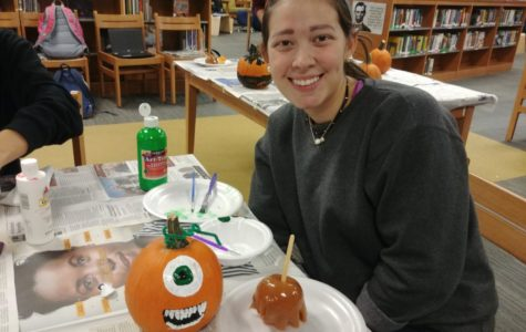 Morgan Sensabaugh adds her finishing touches onto her pumpkin at the Midlo Library's Pumpkin Pizzazz event.