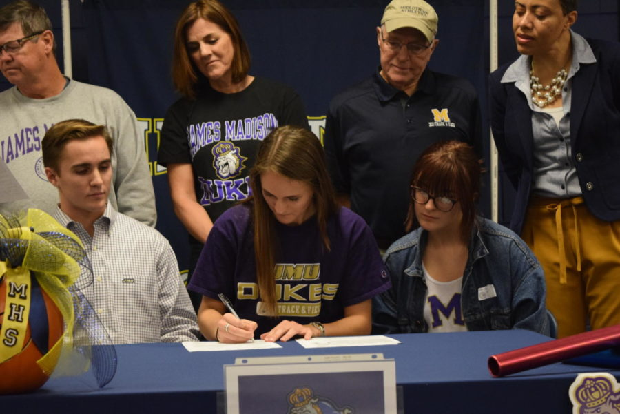 Erin+Babashak+signs+the+paperwork+that+commits+her+to+run+track+and+field+at+JMU.