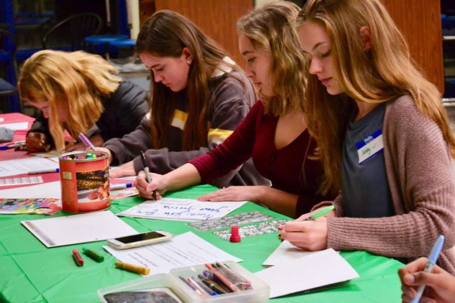 IB students use pens and markers to write colorful cards for the Armed Forces and Meals on Wheels at the IB Potluck