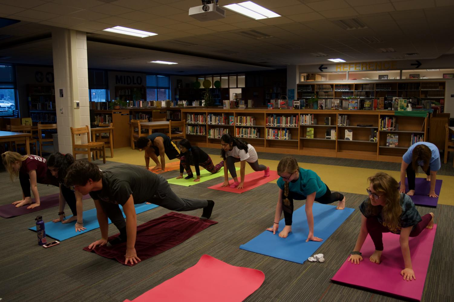 Yoga Club members move into low right lunge pose.