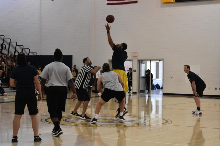 Mr. Jarhon Giddings wins the tip-off against Hunter Klein during the Student vs. Faculty Basketball Game.