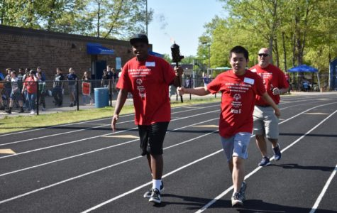 Terrence Reynolds and Danny Huang bring in the ceremonial torch before the 2019 Special Olympics, held at Midlothian High School.