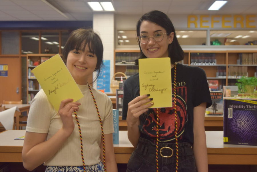 Mayte Losada and Sydney Clevinger show off their graduation cords and bulletins from the German Honor Society induction.