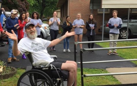 Midlo RAMPS client, Chad, successfully rolls down his newly built ramp and celebrates with  jazz hands and a group applause.