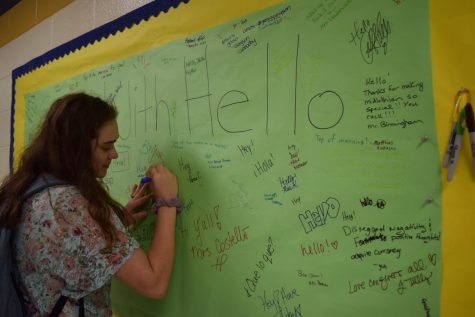 Olivia Eggleston writes her name on the Start With Hello Banner.