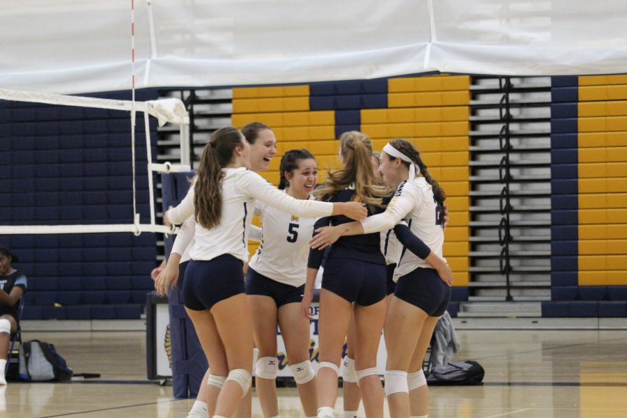Midlo Volleyball celebrates after winning a point against the Titans.