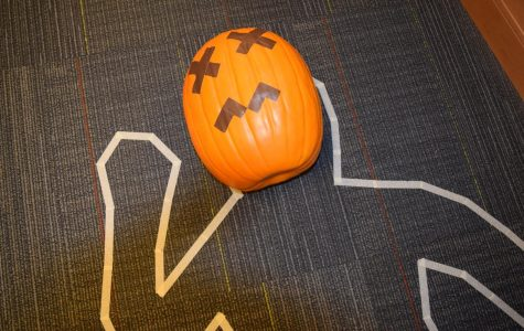 Students work to solve the murder of Pete the Pumpkin at Midlo Library's Paint Your Own Pumpkin event.