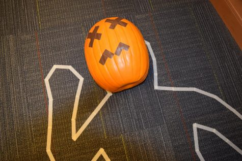 Students work to solve the murder of Pete the Pumpkin at Midlo Library