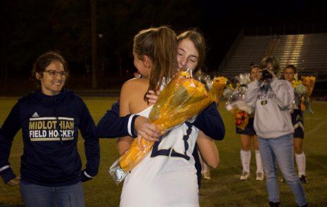 Midlo graduate Lindsey Merillat hands Liza Hopper a bouquet of flowers on Senior Night 2019.