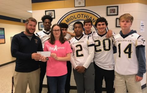 Coach Matt Hutchings, along with members of the Midlo Football team, hands their donation to Katy Sawyer from the Virginia Breast Cancer Foundation.