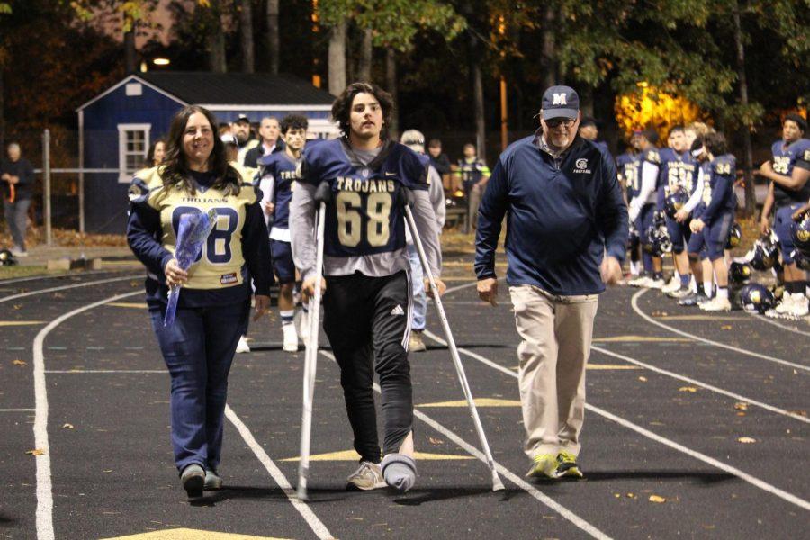 Trey Gholson escorts his parents on Senior Night.