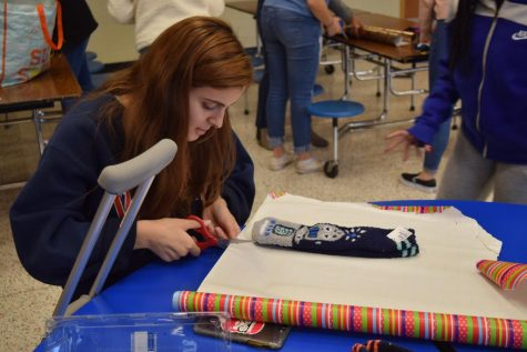 Senior Anna Basir focuses on wrapping  socks at the Spirit Club 2019 Wrapping Party.